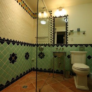 Mediterranean bathroom in Other with a walk-in shower, a two-piece toilet, ceramic tiles, white walls, terracotta flooring, a wall-mounted sink and multi-coloured tiles.