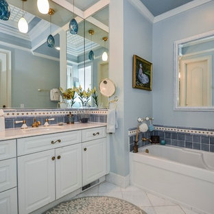 Alcove bathtub - traditional blue tile alcove bathtub idea in Charlotte with an undermount sink, raised-panel cabinets and white cabinets