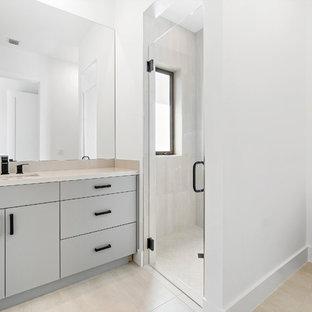 Modelo de cuarto de baño actual con ducha doble, sanitario de una pieza, paredes blancas, suelo beige, ducha con puerta con bisagras y encimeras amarillas