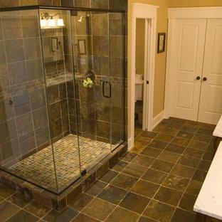 Diseño de cuarto de baño de estilo americano, grande, con lavabo bajoencimera, armarios con paneles lisos, puertas de armario de madera oscura, encimera de mármol, ducha empotrada, sanitario de dos piezas, baldosas y/o azulejos multicolor, baldosas y/o azulejos de piedra, paredes beige y suelo de pizarra