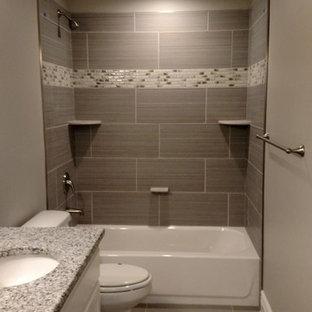Cette photo montre une petite salle d'eau chic avec un placard à porte plane, des portes de placard blanches, une baignoire d'angle, une douche d'angle, un WC à poser, un carrelage gris, un carrelage multicolore, un carrelage blanc, des carreaux de céramique, un mur beige, un sol en carrelage de porcelaine, un lavabo posé et un plan de toilette en granite.
