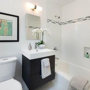 Idee per una stanza da bagno con doccia minimal di medie dimensioni con ante lisce, ante nere, vasca ad alcova, vasca/doccia, WC a due pezzi, piastrelle nere, piastrelle grigie, piastrelle bianche, piastrelle diamantate, pareti bianche e lavabo integrato