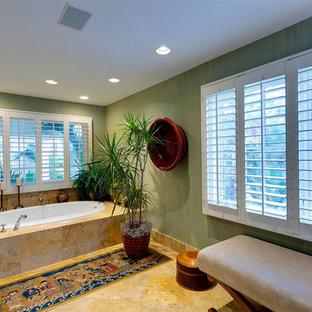 Ejemplo de cuarto de baño principal, exótico, grande, con armarios con paneles empotrados, puertas de armario de madera oscura, bañera encastrada, sanitario de una pieza, paredes verdes, suelo de baldosas de porcelana, lavabo encastrado, encimera de laminado, suelo multicolor y encimeras beige