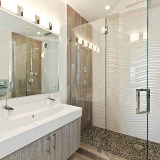 Example of a trendy pebble tile floor alcove shower design in San Francisco with a trough sink and flat-panel cabinets