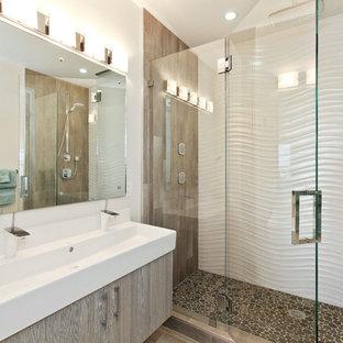 Imagen de cuarto de baño actual con lavabo de seno grande, armarios con paneles lisos, ducha empotrada y suelo de baldosas tipo guijarro