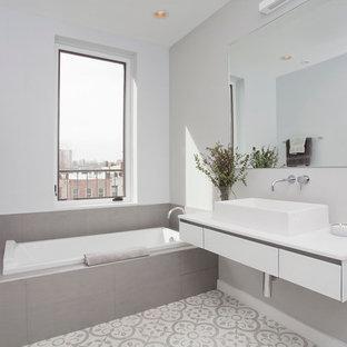 Drop-in bathtub - mid-sized scandinavian gray tile drop-in bathtub idea in New York with a vessel sink and gray walls
