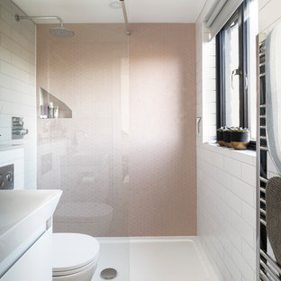 Photo of a small contemporary ensuite bathroom in Sussex with a walk-in shower, a wall mounted toilet, pink tiles, ceramic tiles, white walls, grey floors, an open shower, flat-panel cabinets and white cabinets.