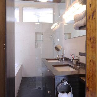 Foto de cuarto de baño principal, contemporáneo, de tamaño medio, con lavabo bajoencimera, armarios con paneles lisos, puertas de armario negras, encimera de ónix, combinación de ducha y bañera, sanitario de una pieza, baldosas y/o azulejos blancos, baldosas y/o azulejos en mosaico, paredes blancas y suelo de pizarra