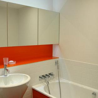 Ispirazione per una piccola stanza da bagno padronale minimal con ante di vetro, ante arancioni, vasca freestanding, piastrelle bianche, piastrelle in ceramica, pareti arancioni, pavimento in gres porcellanato, lavabo a colonna e top in vetro