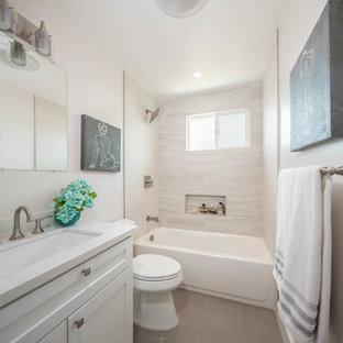 Amerikansk inredning av ett mellanstort vit vitt badrum för barn, med skåp i shakerstil, vita skåp, ett badkar i en alkov, en dusch i en alkov, en toalettstol med hel cisternkåpa, grå kakel, porslinskakel, vita väggar, klinkergolv i porslin, ett undermonterad handfat, bänkskiva i kvarts, grått golv och med dusch som är öppen