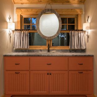 Modelo de cuarto de baño con ducha, rural, de tamaño medio, con armarios con rebordes decorativos, puertas de armario naranjas, sanitario de dos piezas, paredes beige, suelo de madera clara, lavabo bajoencimera, encimera de granito y suelo marrón