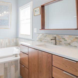 Ejemplo de cuarto de baño principal, vintage, de tamaño medio, con armarios con paneles lisos, puertas de armario de madera oscura, bañera encastrada, baldosas y/o azulejos azules, baldosas y/o azulejos verdes, baldosas y/o azulejos naranja, baldosas y/o azulejos blancos, baldosas y/o azulejos de vidrio, paredes azules, suelo de baldosas de porcelana, lavabo bajoencimera y encimera de cuarcita