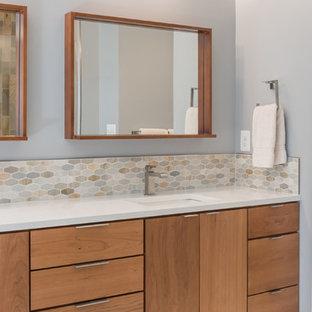 На фото: главная ванная комната среднего размера в стиле ретро с плоскими фасадами, фасадами цвета дерева среднего тона, накладной ванной, синей плиткой, зеленой плиткой, оранжевой плиткой, белой плиткой, стеклянной плиткой, синими стенами, полом из керамогранита, врезной раковиной и столешницей из кварцита с