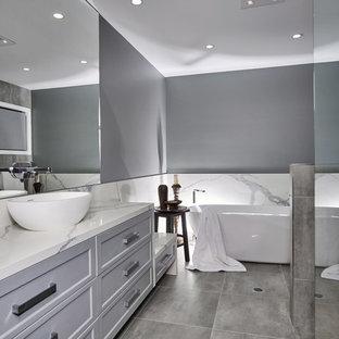 Новый формат декора квартиры: главная ванная комната в стиле модернизм с фасадами в стиле шейкер, серыми фасадами, отдельно стоящей ванной, угловым душем, унитазом-моноблоком, серой плиткой, мраморной плиткой, серыми стенами, полом из терраццо, настольной раковиной, столешницей из искусственного кварца, серым полом, душем с распашными дверями и серой столешницей