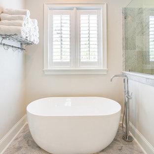 Klassisk inredning av ett stort vit vitt en-suite badrum, med luckor med profilerade fronter, vita skåp, ett fristående badkar, en hörndusch, vit kakel, marmorkakel, vita väggar, marmorgolv, ett undermonterad handfat, marmorbänkskiva, gult golv och dusch med gångjärnsdörr