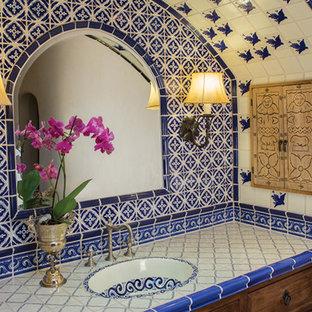 Modelo de cuarto de baño principal, mediterráneo, grande, con lavabo encastrado, armarios con paneles con relieve, puertas de armario de madera en tonos medios, encimera de azulejos, ducha esquinera, baldosas y/o azulejos azules, baldosas y/o azulejos de terracota, paredes beige y suelo de madera en tonos medios