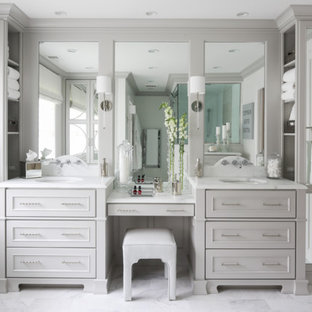 Photo of a large traditional master bathroom in New York with flat-panel cabinets, grey cabinets, a two-piece toilet, white tile, stone tile, grey walls, marble floors, an undermount sink and marble benchtops.