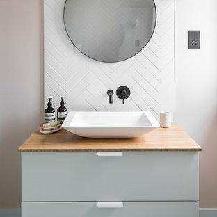 Bild på ett nordiskt beige beige badrum, med släta luckor, vita skåp, vit kakel, vita väggar, ett fristående handfat, träbänkskiva och grönt golv