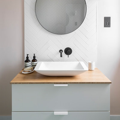 Danish white tile green floor bathroom photo in London with flat-panel cabinets, white cabinets, white walls, a vessel sink, wood countertops and beige countertops