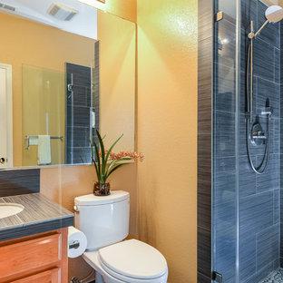 Ispirazione per una piccola stanza da bagno con doccia contemporanea con ante lisce, ante in legno scuro, doccia aperta, WC a due pezzi, piastrelle grigie, piastrelle in gres porcellanato, pareti gialle, pavimento con piastrelle in ceramica, lavabo da incasso e top piastrellato