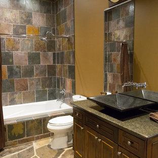 На фото: со средним бюджетом ванные комнаты среднего размера в стиле рустика с фасадами с утопленной филенкой, коричневыми фасадами, накладной ванной, душем над ванной, разноцветной плиткой, плиткой из сланца, полом из сланца, душевой кабиной, настольной раковиной, столешницей из гранита, коричневым полом, шторкой для душа, раздельным унитазом и коричневыми стенами