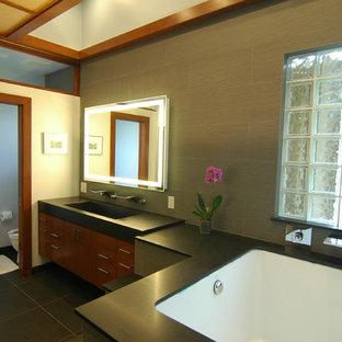 Ejemplo de cuarto de baño de estilo zen con lavabo de seno grande, armarios con paneles lisos, puertas de armario de madera oscura, bañera encastrada sin remate, baldosas y/o azulejos negros y baldosas y/o azulejos de piedra