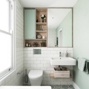 Design ideas for a scandinavian bathroom in London with flat-panel cabinets, green cabinets, a wall mounted toilet, white tiles, metro tiles, green walls, a wall-mounted sink and multi-coloured floors.