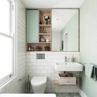 Diseño de cuarto de baño nórdico con armarios con paneles lisos, puertas de armario verdes, sanitario de pared, baldosas y/o azulejos blancos, baldosas y/o azulejos de cemento, paredes verdes, lavabo suspendido y suelo multicolor