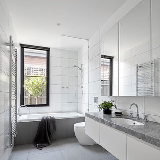 Photo of a large contemporary bathroom in Melbourne with white cabinets, a drop-in tub, a shower/bathtub combo, a wall-mount toilet, white tile, porcelain tile, white walls, porcelain floors, an undermount sink, marble benchtops, grey floor, an open shower, grey benchtops and flat-panel cabinets.