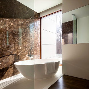 Example of a minimalist brown tile and stone slab freestanding bathtub design in New York with brown walls