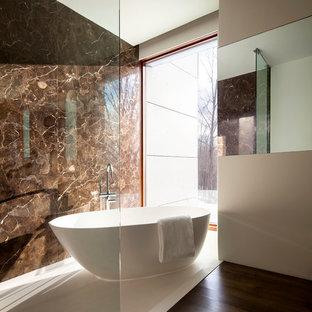 Ejemplo de cuarto de baño minimalista con bañera exenta, paredes marrones, baldosas y/o azulejos marrones y losas de piedra