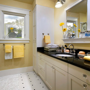 Example of a mid-sized classic master white tile and mosaic tile mosaic tile floor and white floor corner shower design in Detroit with an undermount sink, recessed-panel cabinets, beige cabinets, yellow walls, a two-piece toilet and a hinged shower door