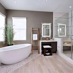 Foto de cuarto de baño principal, minimalista, grande, con armarios con paneles lisos, puertas de armario de madera en tonos medios, bañera exenta, ducha empotrada, baldosas y/o azulejos beige, suelo de baldosas tipo guijarro, paredes grises, suelo de baldosas de porcelana y encimera de acrílico