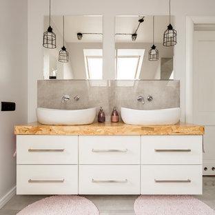 На фото: большая главная ванная комната в современном стиле с плоскими фасадами, белыми фасадами, белыми стенами, настольной раковиной, серым полом, отдельно стоящей ванной, открытым душем, унитазом-моноблоком, белой плиткой, цементной плиткой, мраморным полом, столешницей из дерева, открытым душем и бежевой столешницей с