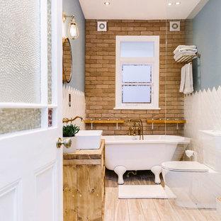 Immagine di una stanza da bagno rustica con vasca con piedi a zampa di leone, WC a due pezzi, pavimento in laminato e lavabo a bacinella