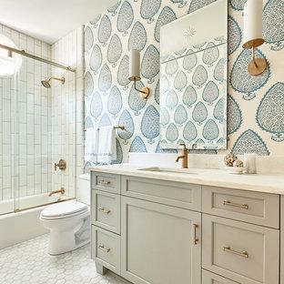 Idee per una stanza da bagno stile marino con ante con riquadro incassato, ante grigie, vasca/doccia, WC a due pezzi, piastrelle bianche, pareti multicolore e porta doccia scorrevole