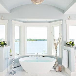 На фото: главные ванные комнаты в морском стиле с отдельно стоящей ванной, плиткой мозаикой, синими стенами и белой плиткой