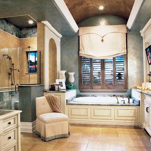 Imagen de cuarto de baño principal, mediterráneo, de tamaño medio, con armarios con paneles empotrados, puertas de armario blancas, bañera encastrada, ducha empotrada, baldosas y/o azulejos beige, baldosas y/o azulejos azules, paredes azules, suelo beige, ducha con puerta con bisagras, sanitario de dos piezas, baldosas y/o azulejos de piedra, suelo de piedra caliza, lavabo bajoencimera y encimera de granito