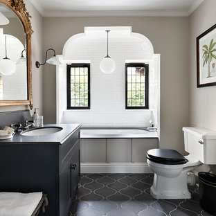 Design ideas for a classic bathroom in London with shaker cabinets, black cabinets, an alcove bath, a two-piece toilet, beige walls, a submerged sink and black and white tiles.