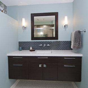 Esempio di una stanza da bagno con doccia minimal con lavabo sottopiano, ante lisce, ante in legno bruno, top in quarzite, piastrelle in ceramica, pareti blu, pavimento con piastrelle a mosaico e piastrelle nere