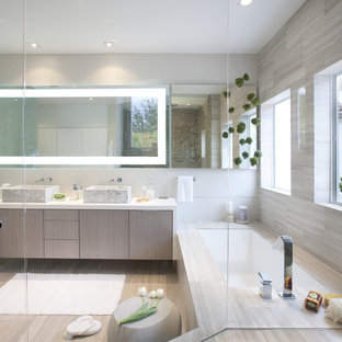 Inspiration for a modern beige tile alcove bathtub remodel in Miami with a vessel sink, flat-panel cabinets and light wood cabinets