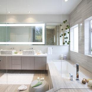 Modernes Badezimmer mit Aufsatzwaschbecken, flächenbündigen Schrankfronten, hellen Holzschränken, Badewanne in Nische und beigefarbenen Fliesen in Miami