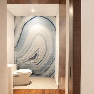 Immagine di una stanza da bagno design con WC monopezzo, piastrelle blu e lastra di pietra