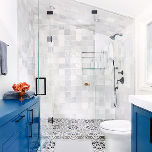 Bild på ett medelhavsstil vit vitt badrum, med skåp i shakerstil, blå skåp, grå kakel, vita väggar och flerfärgat golv