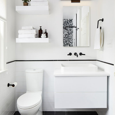 Inspiration for a small contemporary 3/4 white tile black floor bathroom remodel in DC Metro with flat-panel cabinets, white cabinets, white walls, a vessel sink and white countertops