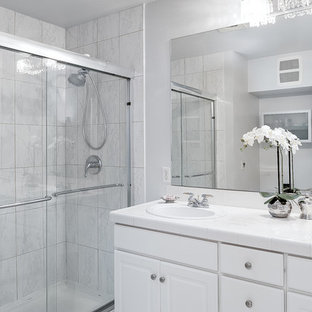 Example of a small transitional master white tile and porcelain tile marble floor doorless shower design in Seattle with flat-panel cabinets, white cabinets, tile countertops, a one-piece toilet, an undermount sink and gray walls