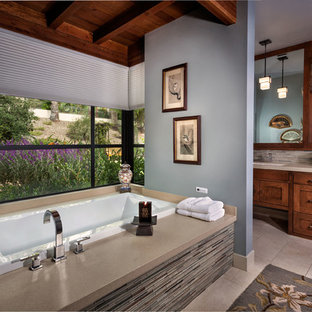 Example of a transitional multicolored tile and matchstick tile drop-in bathtub design in Orange County with an undermount sink, shaker cabinets, dark wood cabinets and beige countertops