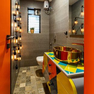 Mittelgroßes Eklektisches Duschbad mit brauner Wandfarbe, Aufsatzwaschbecken, verzierten Schränken, Wandtoilette, grauen Fliesen, Mosaik-Bodenfliesen, beigem Boden und bunter Waschtischplatte in Mumbai