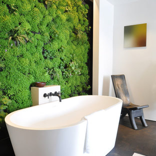 This is an example of a contemporary bathroom in San Francisco with a freestanding bath and green walls.