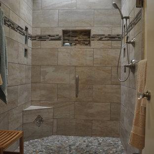 Immagine di una stanza da bagno padronale minimal di medie dimensioni con doccia alcova, piastrelle beige, piastrelle nere, piastrelle marroni, piastrelle grigie, piastrelle multicolore, piastrelle di ciottoli, WC monopezzo, pareti beige, pavimento con piastrelle in ceramica e porta doccia a battente